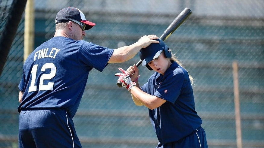 Former baseball player  Steve Finley, left, coaches Melissa Mayeux at a baseball camp in Paderborn, Germany, Wednesday, July 1, 2015 The 16-year-old player on the French U-18 junior national team, made history when she became the first woman on Major League Baseball's international registration list, making her eligible to be signed by Major League teams. (AP Photo/Martin Meissner)