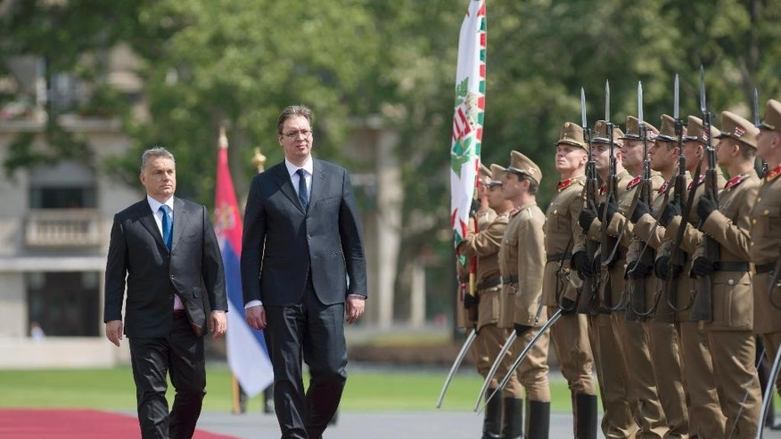 Serbian Prime Minister Aleksandar Vucic, right, and his Hungarian counterpart Viktor Orban inspect the honor guards during the welcoming ceremony in front of the Parliament building in Budapest, Wednesday, July 1, 2015. Vucic is on a one-day official visit to Hungary. (Szilard Koszticsak/MTI via AP)