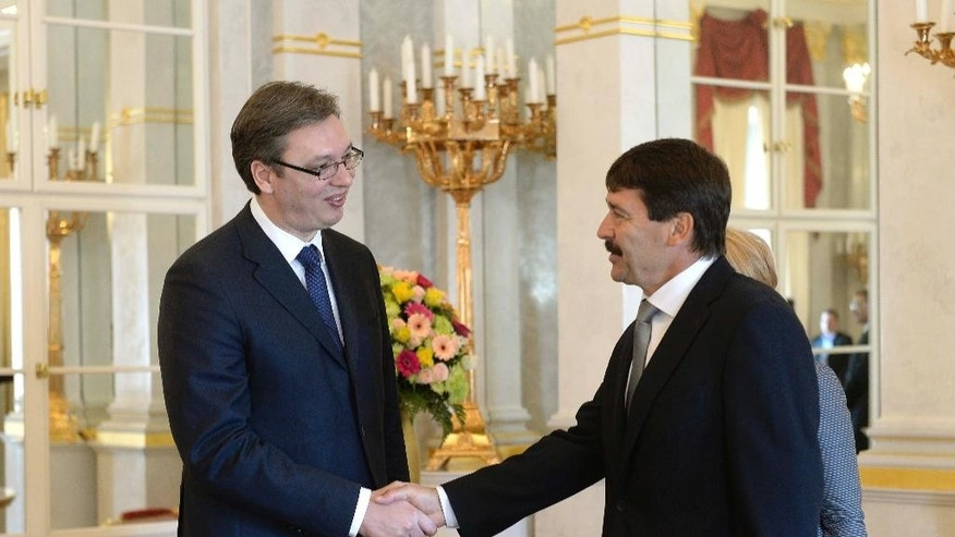 Serbian Prime Minister Aleksandar Vucic, left,  is greeted by President of Hungary Janos Ader during his one-day official visit to Hungary in the presidential Alexander Palace in Budapest, Wednesday, July 1, 2015. Vucic is staying on a one-day official visit to Hungary. (Noemi Bruzak/MTI via AP)