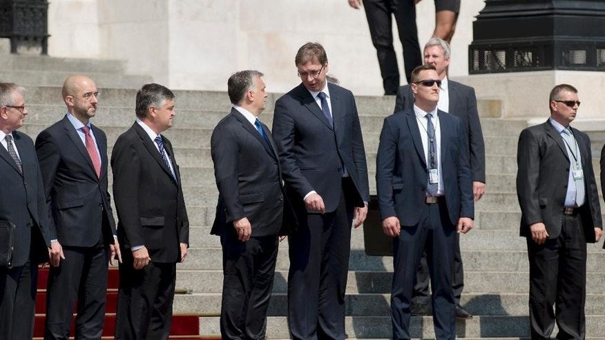 Serbian Prime Minister Aleksandar Vucic, fourth right, chats with his Hungarian counterpart Viktor Orban, fouth left, during the welcoming ceremony in front of the Parliament building in Budapest, Wednesday, July 1, 2015. Vucic is on a one-day official visit to Hungary. (Szilard Koszticsak/MTI via AP)