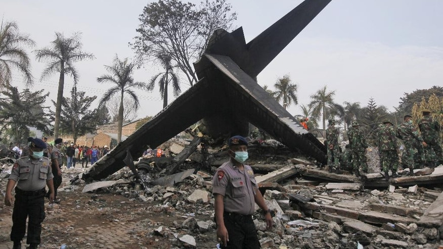 A relative weeps near body bags containing the remains of the victims of a military cargo plane that crashed onto a residential area on Tuesday, at a hospital in Medan, North Sumatra, Indonesia, Wednesday, July 1, 2015. The C-130 Hercules crashed shortly after takeoff on June 30 in the country's third largest city. (AP Photo/Binsar Bakkara)