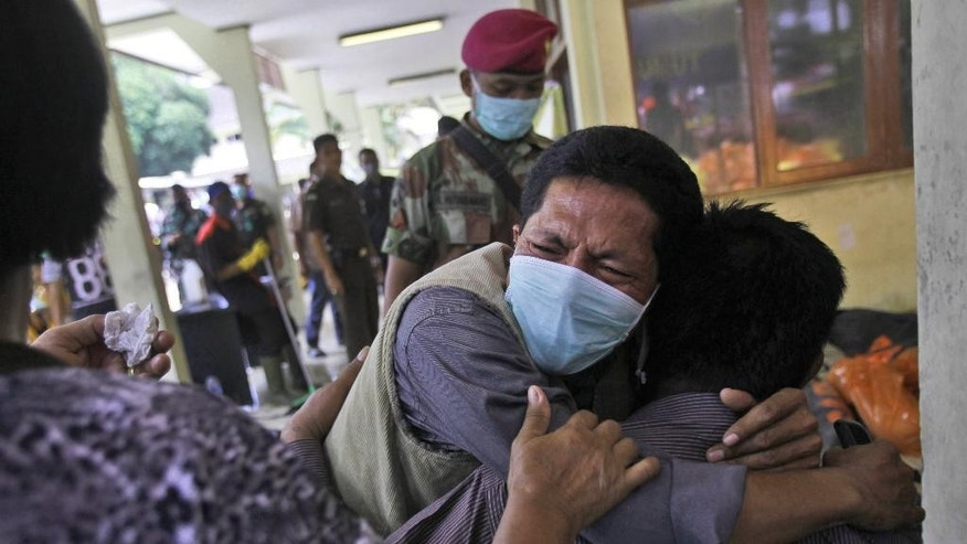 Relatives of the victims of a military cargo plane that crashed onto a residential area on Tuesday console each other at a hospital in Medan, North Sumatra, Indonesia, Wednesday, July 1, 2015. The C-130 Hercules crashed shortly after takeoff on June 30 in the country's third largest city. (AP Photo/Binsar Bakkara)