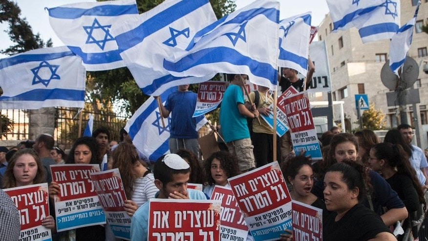 Israelis hold signs and wave flags during a demonstration outside the prime minister's residence in Jerusalem on Wednesday, July 1, 2015. Several hundred Israelis demonstrated in Jerusalem on Wednesday calling on Prime Minister Benjamin Netanyahu to act against recent Palestinian attacks against Israelis, of which a shooting attack at a West Bank settlement killed an Israeli man last week. (AP Photo/Dan Balilty)