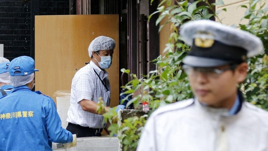 Japanese police search the apartment of the man who set himself on fire on a high-speed bullet train Tuesday on a famed Japanese Shinkansen bullet train, in Tokyo, Wednesday, July 1, 2015.  The man killed himself and another passenger. The shocking incident Tuesday occurred as the super-express train approached Odawara, just west of Tokyo, as it headed to Osaka. (Kyodo News via AP Photo) JAPAN OUT, MANDATORY CREDIT