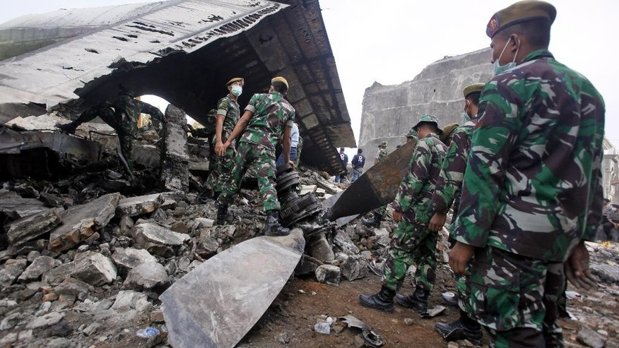 Indonesian soldiers search for victims at the site where an Indonesian air force transport plane crashed in Medan, North Sumatra, Indonesia, Wednesday, July 1, 2015. The Hercules C-130 plane crashed into a residential neighborhood in the country's third-largest city on June 30. (AP Photo/Binsar Bakkara)