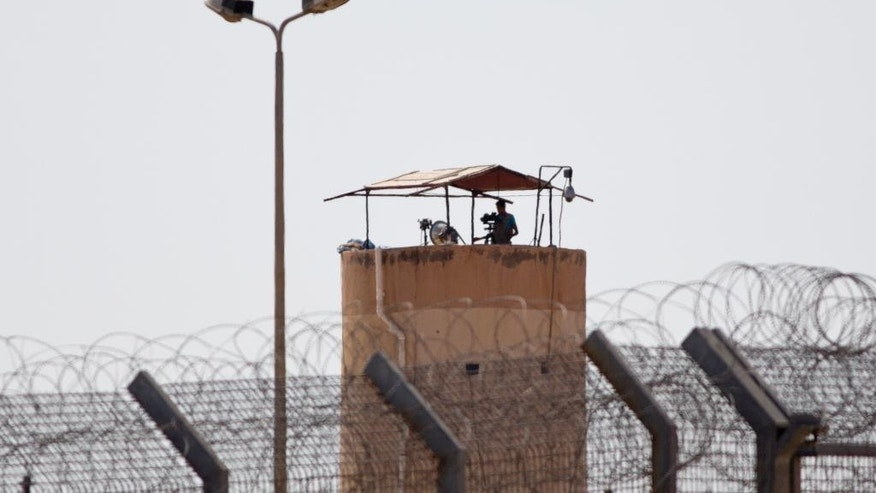 An Egyptian soldier watches from a post in Egypt's northern Sinai Peninsula, as seen from the Israel-Egypt border, in Kerem Shalom town, southern Israel, Wednesday, July 1, 2015. Islamic militants on Wednesday unleashed a wave of simultaneous attacks, including suicide car bombings, on Egyptian army checkpoints in the restive northern Sinai Peninsula, killing tens of soldiers, security and military officials said. (AP Photo/Ariel Schalit)