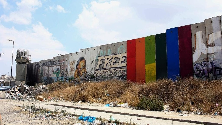 This Monday, June 29, 2015 photo provided by Palestinian artist Khaled Jarrar shows his painting of a rainbow flag on six slabs of the West Bank separation barrier in the West Bank city of Ramallah. The artist, Jarrar, said Tuesday his art was meant as a reminder that Palestinians live under Israeli occupation, at a time when gay rights are in the news after the U.S. allowed same-sex weddings. (Khaled Jarrar via AP)