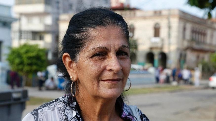 Elba Gil, 61, housewife, poses for a photo in Havana, Cuba, Wednesday, July 1, 2015. Eleven years ago, Gil cried for a week when her daughter left to live in the United States. As her last child remaining on the island now prepares to make the same move soon with her own family, Gil feels more nostalgic than anything. That's because improved political ties are making it easier for families divided by the Florida Straits to stay in touch. (AP Photo/Desmond Boylan)
