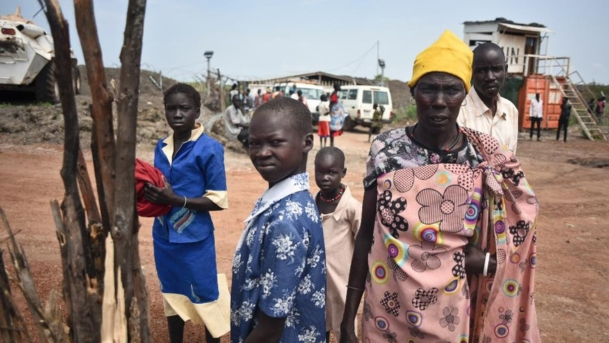 In this photo taken Friday, June 26, 2015, a displaced family arrives at the UN base in Bentiu, South Sudan. South Sudan's army has burned people alive, raped and shot girls, and forced tens of thousands from their homes, according to interviews with survivors by The Associated Press and corroborated by human rights groups. (AP Photo/Jason Patinkin)