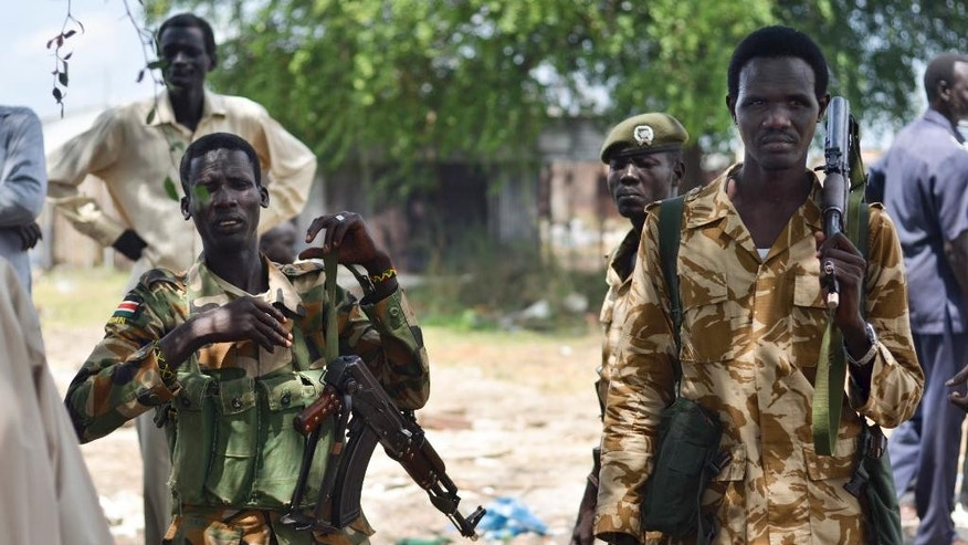 In this photo taken Wednesday, June 24, 2015, South Sudanese government soldiers patrol in Bentiu town, South Sudan. South Sudan's army has burned people alive, raped and shot girls, and forced tens of thousands from their homes, according to interviews with survivors by The Associated Press and corroborated by human rights groups. (AP Photo/Jason Patinkin)