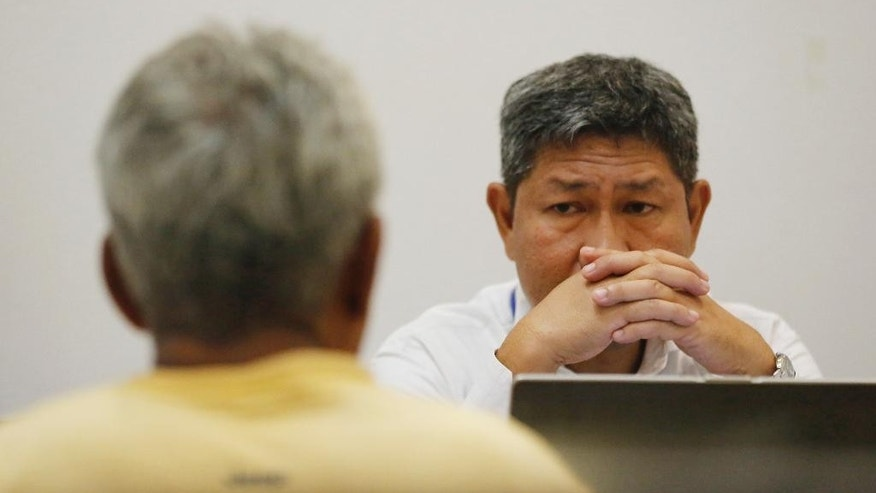 An investigator of Thailand's Department of Special Investigation interrogates a key suspect in a human trafficking ring Samruay Chatkrod, left, in Bangkok, Thailand, Wednesday, July 1, 2015. Thai officials said Wednesday they arrested two key figures in a human trafficking ring that provides slave crews for the country's fishing boats, the latest move in a crackdown on widespread labor abuses in Southeast Asia's fishing industry. (AP Photo/Sakchai Lalit)