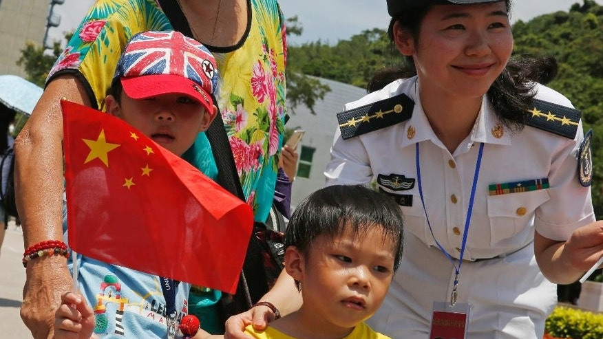 Visitors pose with a Chinese People's Liberation Army (PLA) personnel at the open day of Stonecutter Island Navy Base in Hong Kong to mark the 18th anniversary of the Hong Kong handover to China in Hong Kong, Wednesday, July 1, 2015. (AP Photo/Kin Cheung)