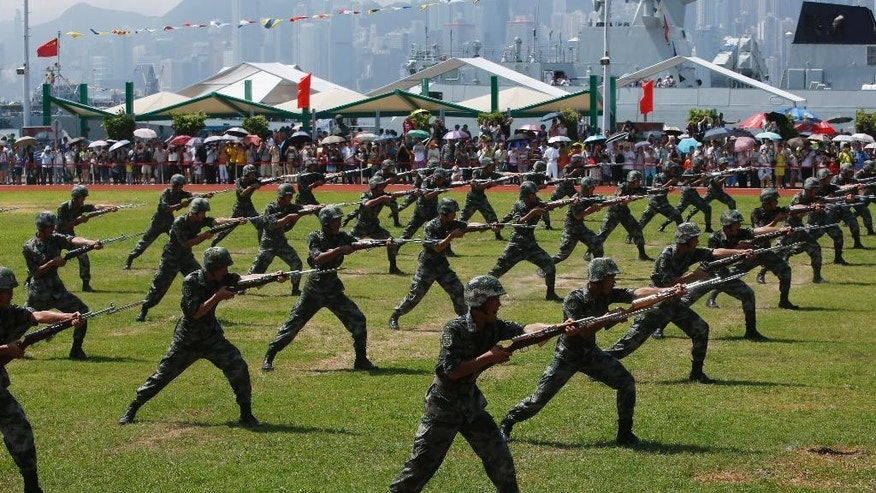 Chinese People's Liberation Army (PLA) personnel demonstrate during the open day of Stonecutter Island Navy Base in Hong Kong to mark the 18th anniversary of the Hong Kong handover to China in Hong Kong, Wednesday, July 1, 2015. (AP Photo/Kin Cheung)
