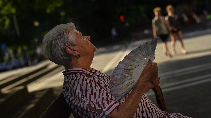 A woman uses a fan to cool off in the shade on a hot summer day, in Pamplona, northern Spain, Tuesday, June 30, 2015. A mass of hot air moving north from Africa is bringing a heat wave to Europe, with France the next in line for a scorching day.  Forecasters said southern France could see temperatures over 40 degrees Celsius on Tuesday, a day after Cordoba in southern Spain recorded 43.7 degrees Celsius (110.66 Fahrenheit).  (AP Photo/Alvaro Barrientos)