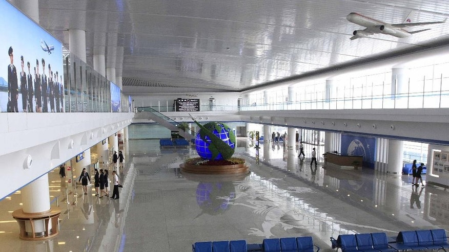 Staff members walk along the completed interiors of the new international airport terminal building at Pyongyang airport, Wednesday, July 1, 2015, in Pyongyang, North Korea. The unveiling Wednesday underscores an effort to attract more tourists and to spruce up the country ahead of the celebration of a major anniversary of the founding of its ruling Worker's Party in October this year. (AP Photo/Kim Kwang Hyon)