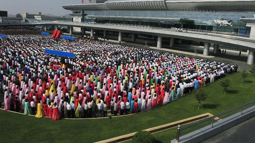 People gather during an opening ceremony of the new international airport terminal building at Pyongyang airport, Wednesday, July 1, 2015, in Pyongyang, North Korea. The unveiling Wednesday underscores an effort to attract more tourists and to spruce up the country ahead of the celebration of a major anniversary of the founding of its ruling Worker's Party in October this year. (AP Photo/Kim Kwang Hyon)