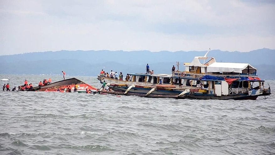The Philippine Coast Guard rescues boat passengers after a ferry boat capsized in choppy waters, on Thursday, July 2, 2015, in Ornoc, Philippines. The Ferry had just departed the port of Ornoc on Leyte heading to Camotes islands when it was capsized by large waves, the coast guard said. (AP Photo)
