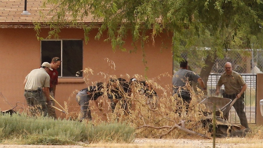 In this July 1, 2015 photo, Pinal County sheriff's deputies and investigators dig behind a home in Maricopa, Ariz., looking for clues in the disappearance of Michael and Tina Careccia. The bodies of the couple were recovered from a property near their home. Pinal County Sheriff Paul Babeu says officers arrested 38-year-old Jose Valenzuela and booked him into jail on suspicion of first-degree murder. (David Kadlubowski/The Arizona Republic via AP) MARICOPA COUNTY OUT - NO MAGS- NO SALES - MANDATORY CREDIT