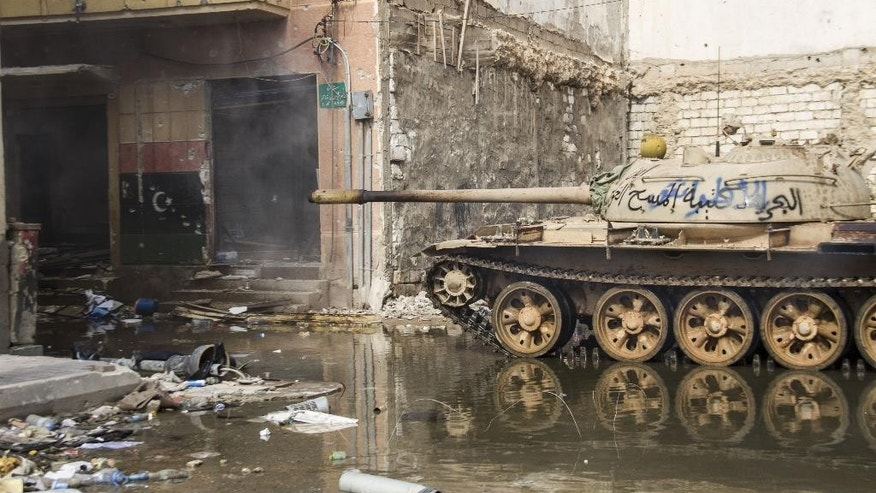 In this photo taken March 3, 2015, a tank stands amongst damaged buildings in Benghazi, Libya. Destruction has permeated the North African country since the civil war ousted Moammar Gadhafi four years ago. For Benghazi, the past year was the worst.   (AP Photo/Mohamed Salama)