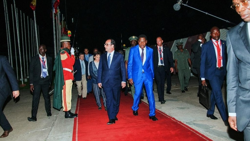 French President Francois Hollande, center left,  arrives in the early hours of the morning at Cotonou airport in  Cotonou, Benin, Thursday, July 2, 2015. French President Francois Hollande will visit Benin , Angola and Cameroon for talks on economic and social issues. (AP Photo/Valentin Salako)