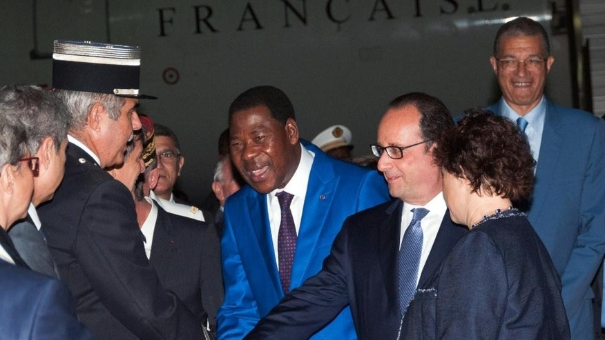 French President Francois Hollande, center right, greets people as he arrives in the early hours of the morning at Cotonou airport in Cotonou, Benin, Thursday, July 2, 2015. French President Francois Hollande will visit Benin, Angola and Cameroon for talks on economic and social issues. (AP Photo/Valentin Salako)