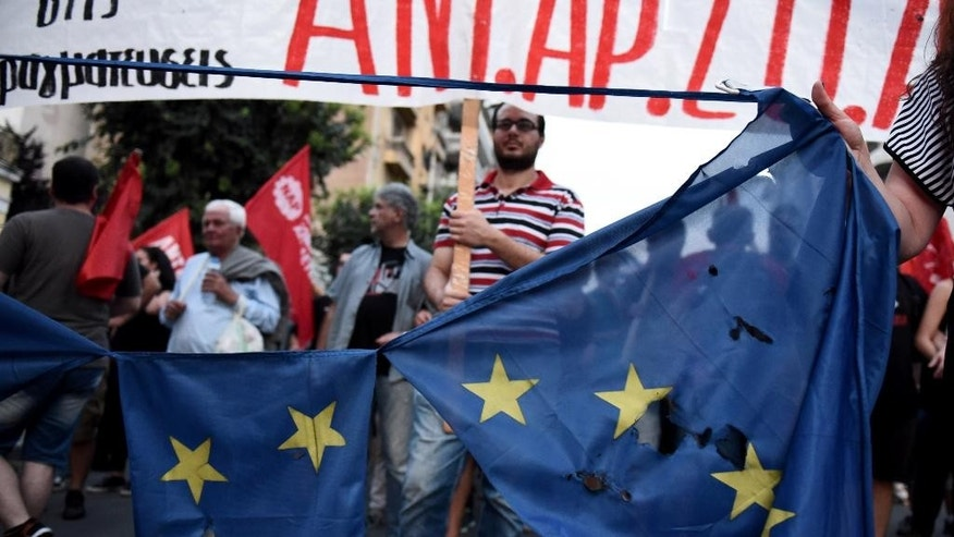 Demonstrators destroy a European flag during a rally by supporters of the no vote to the upcoming referendum in the northern Greek port city of Thessaloniki, Wednesday, July 1, 2015. Eurozone finance ministers decided Wednesday to break off talks on more aid for Greece until after it holds a weekend referendum, even as the Greek government pressed ahead with plans to let the people decide whether to accept more austerity measures in exchange for a rescue deal. (AP Photo/Giannis Papanikos)