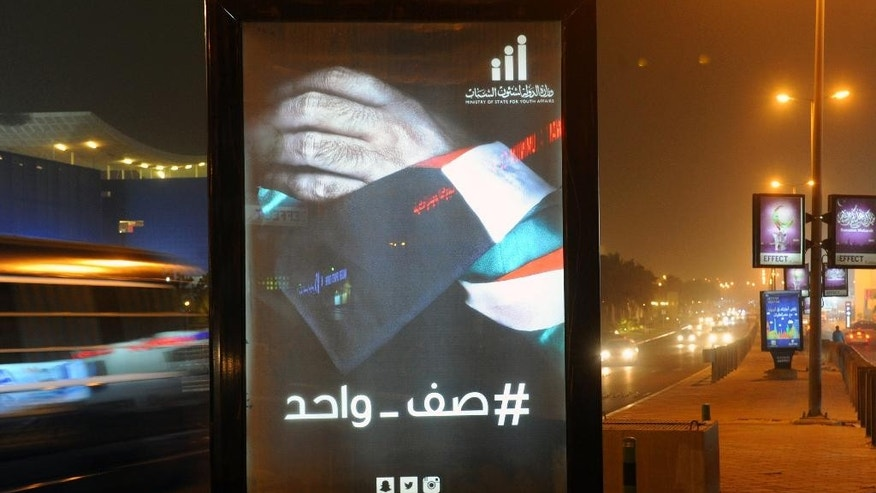 "In this Wednesday, June 1, 2015 photo, a billboard in Kuwait City shows the Kuwaiti flag wrapped around a hand, with the slogan: ""We stand as one,"" as part of a billboard campaign launched up 24 hours after a suicide attack on a Shiite mosque on Friday. An Islamic State sympathizer's deadly bombing in a packed Kuwaiti mosque last week was designed to fit an all-too-familiar pattern: extremists attack Shiites to stoke sectarian hatred and then proclaim themselves the defenders of Sunnis against those they denounce as heretics. This time the attack seems to have backfired, at least for now. Instead of fueling the kind of sectarian animosity that has devastated Iraq and Syria, the Kuwait attack has reawakened a sense of national solidarity not seen since Saddam Hussein's 1990 invasion.  (AP Photo)"