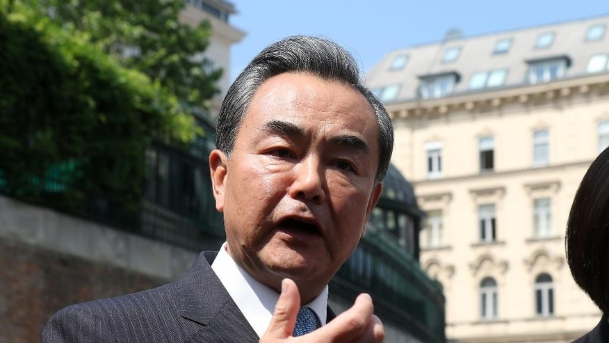 Chinese Foreign Minister Wang Yi  informs the media in front of Palais Coburg where closed-door nuclear talks with Iran take place in Vienna, Austria, Thursday, July 2, 2015. (AP Photo/Ronald Zak)