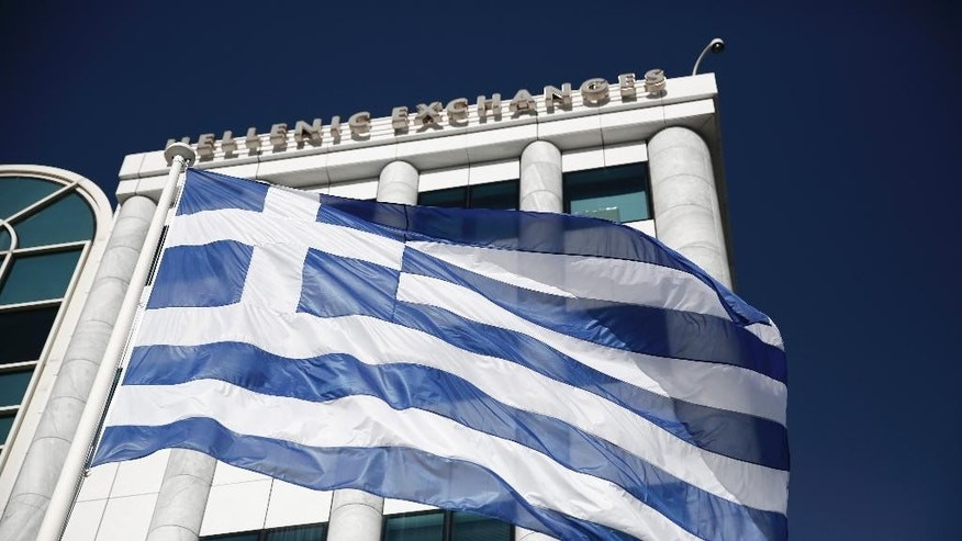 FILE - In this  Feb. 3, 2015, file photo, a Greek flag flies outside the Athens Stock Exchange. In 2012, financial markets were rattled by the possibility Greece would elect a left-wing government, default on their debts and drop the euro currency. In 2015, the left-wing party, Syriza, holds power in Athens. Greece actually did miss a loan payment to the International Monetary Fund late Tuesday, June 30, 2015. And the nation's future in the eurozone hinges precariously on a referendum Sunday, July 5, 2015. (AP Photo/Petros Giannakouris, File)