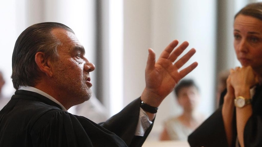 Franck Berton, lawyer of Dominique Cottrez, gestures in the court shortly before the verdict in the case, Thursday, July 2, 2015 in Douai, northern France. A Frenchwoman accused of killing eight of her newborns over more than a decade has been sentenced to nine years in prison after a one-week dramatic and teary murder trial. After deliberating a few hours in the northern city of Douai, the jury on Thursday returned its verdict - twice as lenient as the 18-year prison term asked by the prosecutor against Dominique Cottrez, a 51-year-old married mother. The jury decided that her judgment was impaired at the time of the killings.(AP Photo/Michel Spingler)