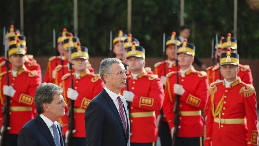 NATO Secretary General Jens Stoltenberg, right, and Romanian defense minister Mircea Dusa, left, review a honor guard in Bucharest, Romania, Thursday, July 2, 2015. Stoltenberg is meeting top officials in Romania and will inspect a site where the alliance will build a facility dubbed the NATO Force Integration Unit that is similar to ones planned in Poland, Bulgaria and the three Baltic states — Estonia, Latvia and Lithuania, in reaction to the crisis in Ukraine.(AP Photo/Vadim Ghirda)