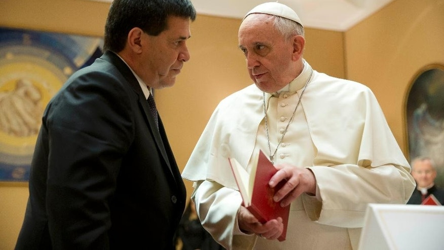 "FILE - In this April 29, 2014 file photo, Pope Francis presents Paraguay's President Horacio Cartes with the book of the gospel during a private audience at the Vatican. Pope Francis is taking his ""church for the poor"" to three of South America's poorest and most peripheral countries, making a grueling, week-long trip that will showcase the pope at his unpredictable best: speaking his native Spanish on his home turf about issues closest to his heart. (AP Photo/Gregorio Borgia, Pool, File)"