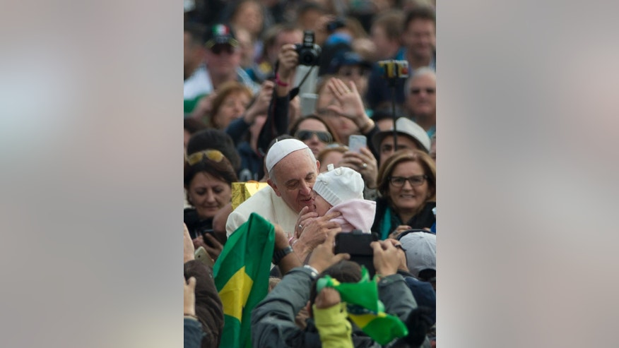"FILE - In this Oct. 29, 2014 file photo, Pope Francis kisses a baby as he arrives for his weekly general audience in St. Peter's Square at the Vatican. Pope Francis is taking his ""church for the poor"" to three of South America's poorest and most peripheral countries, making a grueling, week-long trip that will showcase the pope at his unpredictable best: speaking his native Spanish on his home turf about issues closest to his heart. (AP Photo/Alessandra Tarantino, File)"