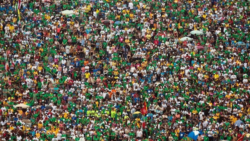 "FILE - In this July 28, 2013 file photo, people attend the World Youth Day's closing Mass celebrated by Pope Francis on the Copacabana beachfront, in Rio de Janeiro, Brazil. Pope Francis is taking his ""church for the poor"" to three of South America's poorest and most peripheral countries, making a grueling, week-long trip that will showcase the pope at his unpredictable best: speaking his native Spanish on his home turf about issues closest to his heart. (AP Photo/Felipe Dana, File)"
