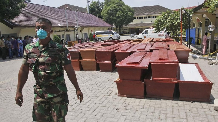 "A soldier walks past coffins prepared for the victims of the military plane crash in Medan, North Sumatra, Indonesia, Thursday, July 2, 2015. The aging Indonesian military transport plane that crashed into a residential neighborhood of Medan had a propeller ""abnormality"" that indicates an engine stalled, the air force chief said Thursday. (AP Photo/Binsar Bakkara)"