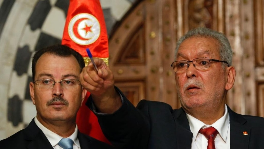 Kamel Jendoubi, Minister to the Prime Minister in charge of Relations with Constitutional Bodies and the Civil Society, right, gestures during a press conference in Tunis, Tunisia, Thursday, July 2, 2015. The Islamic State group claimed responsibility for the attack, in which a Tunisian student opened fire on a beach in the resort of Sousse. The attacker was later killed by police. (AP Photo/Darko Vojinovic)