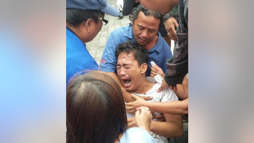 Police and rescuers comfort a crying passenger after being brought to the pier upon his rescue from a sinking passenger ferry Thursday, July 2, 2015 in Ormoc city, central Philippines. Coast Guard officials say the boat capsized minutes after it left a central Philippine port in choppy waters, leaving at least 36 dead and 26 others missing. They said at least 127 people from the M/B Kim Nirvana were rescued by nearby fishing boats and coast guard personnel or swam to safety off Ormoc city on Leyte Island. (AP Photo/John Pilapil)
