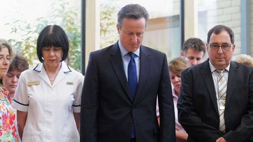 July 3, 2015: Britain's Prime Minister, David Cameron, centre, stands in silence during a visit to Chipping Norton Health Centre in his constituency in Witney, England, as Britain remembers the victims of the Tunisia terror attack with a minute's silence. (AP)