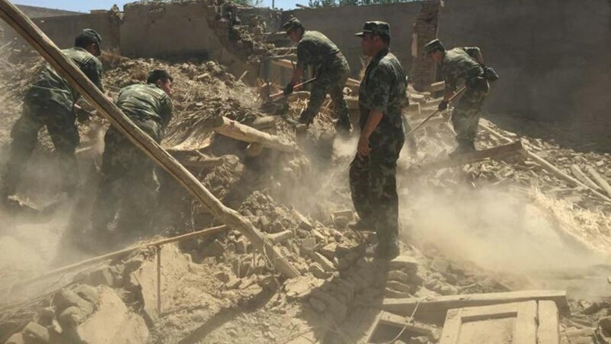 In this photo taken on July 3, 2015 and released by China's Xinhua News Agency, soldiers carry out rescue work in Pishan county, northwest China's Xinjiang Uygur Autonomous Region.  A magnitude 6.5 earthquake shook China's far-western region of Xinjiang and collapsed thousands of houses, officials said Saturday, July 4, 2015. (Xu Runxian/Xinhua via AP) NO SALES