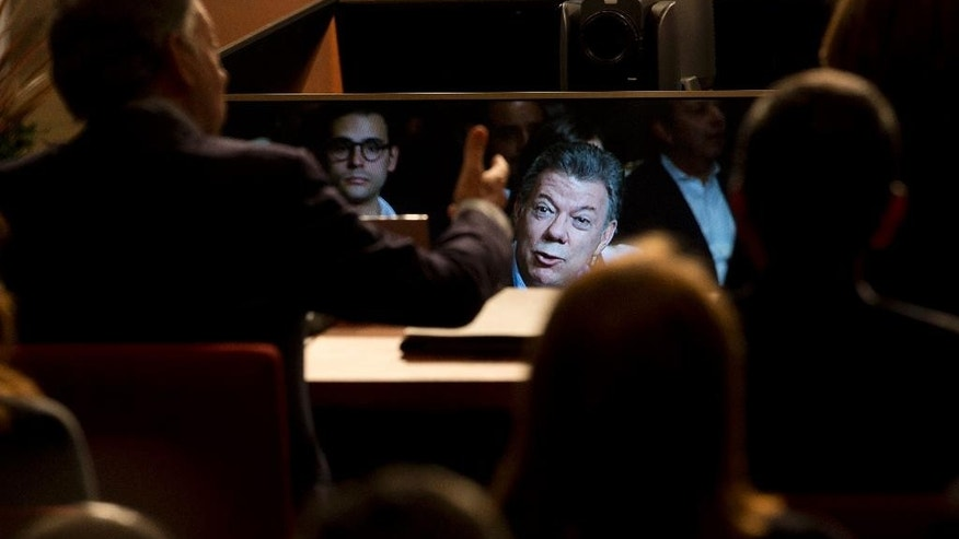 Colombia's President Juan Manuel Santos is seen reflected on a sheet of glass as delivers a speech during the inauguration of the Presidential Pacific Alliance Summit in Paracas, Peru, Thursday, July 2, 2015. (AP Photo/Rodrigo Abd)