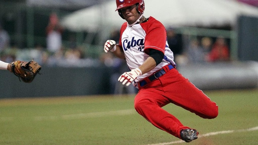 FILE - In this Feb. 7, 2015 file photo, Cuba's Yadiel Hernandez slides safe at the home plate during a Caribbean Series baseball semifinal game against Venezuela in San Juan, Puerto Rico. Cuba is confirming that two baseball players, including Hernandez, have defected while in the United States for a series of friendly games against U.S. collegians. (AP Photo/Ricardo Arduengo, File)