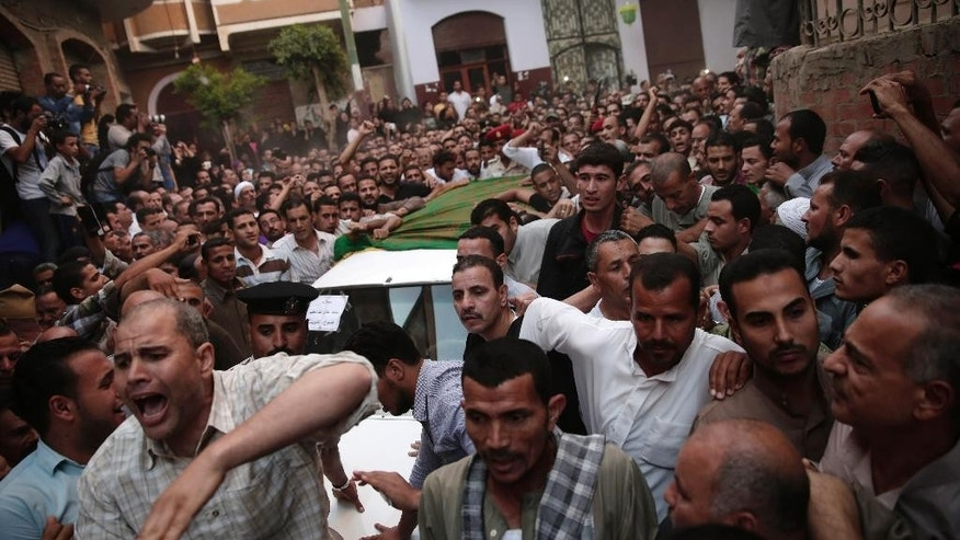 FILE - In this Thursday, July 2, 2015, file photo, Egyptians surround a vehicle carrying the coffin of 1st Lt. Mohammed Adel Abdel Azeem, killed in an attack by Islamic militants in the Sinai, during the funeral procession at his home village Tant Al Jazeera in Qalubiyah, north of Cairo, Egypt. When Abdel-Fattah el-Sissi  led the army's overthrow of Egypt's Islamist president two years ago, he promised to usher in new stability for the country. Instead, now President el-Sissi is facing an even tougher challenge: An Islamic militant insurgency that unleashed its worst violence yet the past week.  (AP Photo/Hassan Ammar, File)