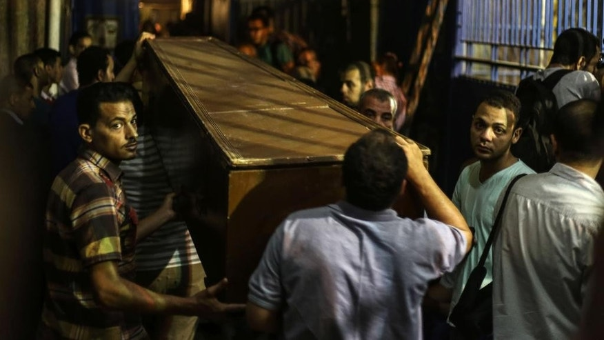 FILE - In this Wednesday, July 1, 2015 file photo, relatives of men who were killed in a raid on a Cairo apartment carry one of their coffin's, outside Zeinhom morgue in Cairo, Egypt. When Abdel-Fattah el-Sissi  led the army's overthrow of Egypt's Islamist president two years ago, he promised to usher in new stability for the country. Instead, now President el-Sissi is facing an even tougher challenge: An Islamic militant insurgency that unleashed its worst violence yet the past week. (AP Photo/Mohamed El Raai, File)