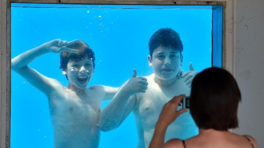 Julian, left, is photographed by his mother with friend Gianluca, right, under water at a public pool in Gelsenkirchen, Germany, on a hot Friday, July 3, 2015. Germany faces a heat wave with temperatures up to 38 degrees Celsius  (100 degrees Fahrenheit) at the weekend. (AP Photo/Martin Meissner)