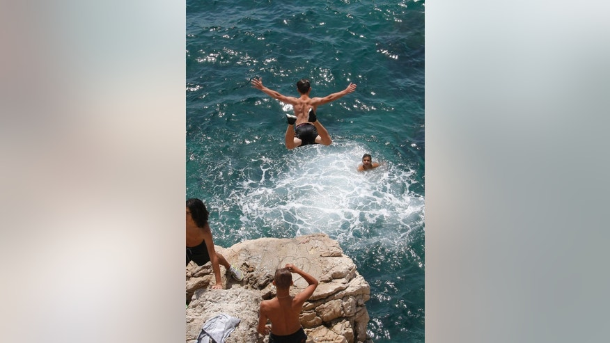 People dive and swim into the Mediterranean sea, in Marseille, southern France, Thursday, July 2, 2015. A mass of hot air moving north from Africa is bringing unusually hot weather to Western Europe, with France in recent days. Temperatures in Nice rose to 30 degrees Celsius (86 Fahrenheit). (AP Photo/Claude Paris)