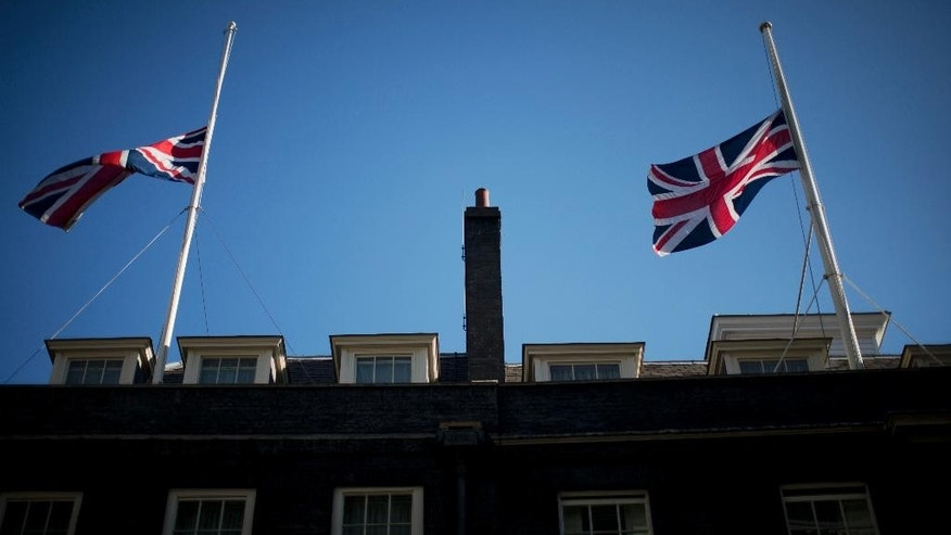 Union flags fly at half-staff on the roof of 10 Downing Street in London, to mark an official day of mourning one week since the deadly Tunisia beach attack that killed 38 people Friday, July 3, 2015. (AP Photo/Matt Dunham)