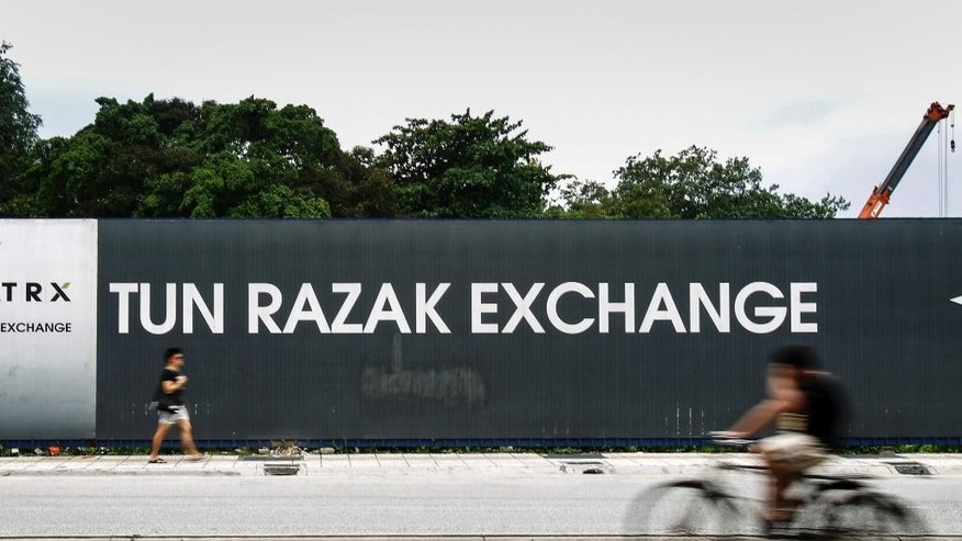 In this May 14, 2015 photo, Malaysians pass by a billboard for the Tun Razak Exchange, a development by state investment fund 1 Malaysia Development Berhad (1MDB)  in Kuala Lumpur, Malaysia. Malaysia's state investment fund 1MDB says it has never provided any funds to Prime Minister Najib Razak, denying reports that entities linked to the fund had funneled $700 million ($2.6 billion) into Najib's personal accounts. (AP Photo/Joshua Paul)