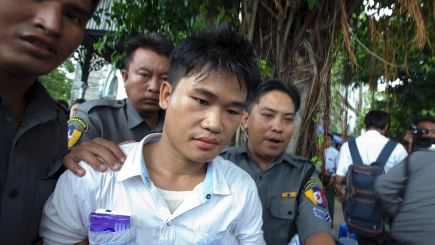 Saw Myint Lwin, in white shirt, escorted by Myanmar police officers, leaves a court after receiving sentence Friday, July 3, 2015, in Yangon, Myanmar. The court ordered Saw Myint Lwin linked to the 2013 bombing at Trader's Hotel, one of the country's most prestigious hotels, to serve life imprisonment plus five years of hard labor. (AP Photo/Khin Maung Win)
