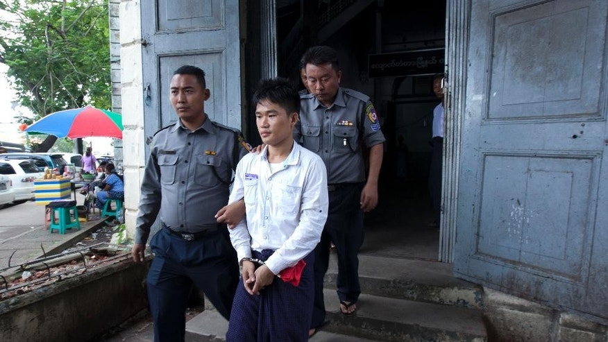 Saw Myint Lwin, center, escorted by Myanmar police officers, leaves a court after receiving sentence Friday, July 3, 2015, in Yangon, Myanmar. The court ordered Saw Myint Lwin linked to the 2013 bombing at Trader's Hotel, one of the country's most prestigious hotels, to serve life imprisonment plus five years of hard labor. (AP Photo/Khin Maung Win)