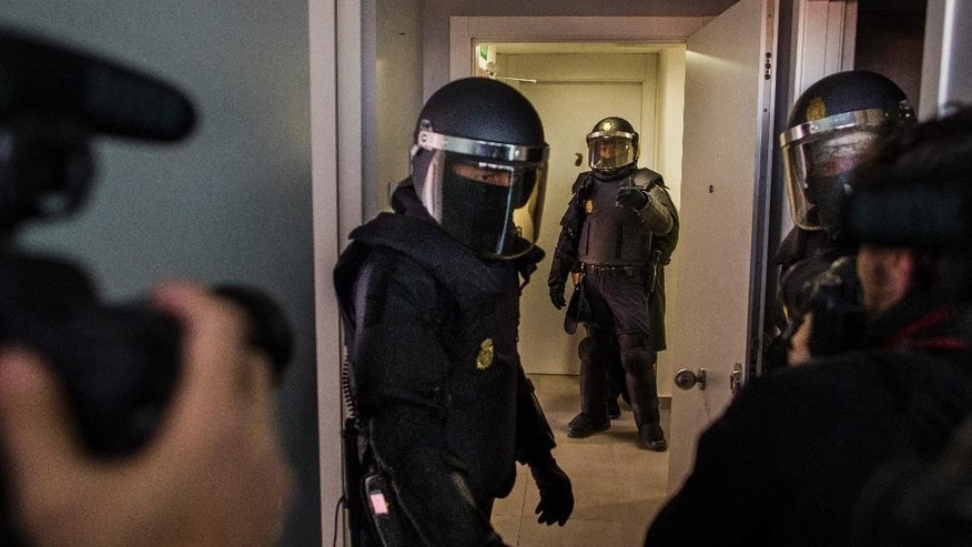 "In this picture taken on Friday, Jan. 23, 2015, a photographer and a camera man record as riot police enter the apartment to evict Cecilia Paredes, her husband and children including a one month old baby in Madrid, Spain. The wide-ranging public security law dubbed ""Gag Law"" has a clause specifying that people can be fined as much as 30,000 euro (US dlrs 33,000) for ""unauthorized use"" of images of working police that could endanger their security or hinder their ability to successfully complete police operations. (AP Photo/Andres Kudacki)"